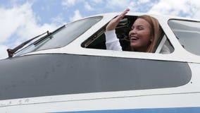 Piękny młoda dziewczyna pilota obsiadanie przy kontrola samolot, spojrzenia out okno zbiory