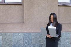Piękny młoda dziewczyna przedsiębiorca trzyma laptop i pracy, rozwiązują Obrazy Royalty Free