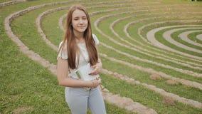 Piękny młoda dziewczyna uczeń stoi w dużym zielonym stadium z podręcznikiem i notatki, ono uśmiecha się, Odpoczynek podczas nauki zbiory