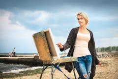 Piękny młoda kobieta obraz na tle niebo i morze Pojęcie twórczość zdjęcia stock