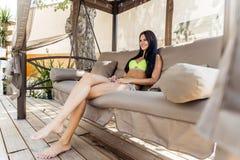 Piękny młodej damy podcieniowanie herself od słońca w dużej huśtawce zdjęcie royalty free