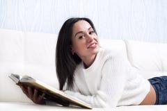 Piękny młodej dziewczyny czytelniczej książki lying on the beach na leżance Fotografia Stock