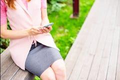 Piękny młodej dziewczyny obsiadanie na drewnianej ławce w otwartym Patrzejący telefon komórkowy kobiet ręk słonecznego dnia ziele zdjęcie royalty free