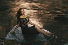 Piękny młodej dziewczyny obsiadanie na kamieniu rzeką w parzysty, równy zdjęcie stock