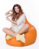 Piękny młodej dziewczyny obsiadanie na pomarańczowej poduszce Fotografia Royalty Free