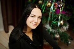 Piękny młodej dziewczyny obsiadanie przy choinką Fotografia Stock
