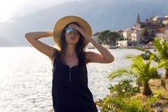 Piękny młodej dziewczyny obsiadanie w kapeluszu na tle góry i morze Fotografia Royalty Free