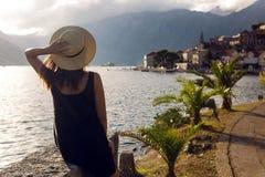 Piękny młodej dziewczyny obsiadanie w kapeluszu na tle góry i morze Obrazy Royalty Free