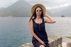 Piękny młodej dziewczyny obsiadanie w kapeluszu na tle góry i morze Zdjęcie Stock