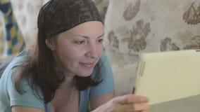 Piękny młodej dziewczyny use pastylki komputeru ono uśmiecha się zbiory wideo
