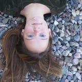 Piękny młodej dziewczyny zakończenia lying on the beach na dennych otoczakach Denne gry Obrazy Stock