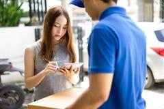 Piękny młodej kobiety dostawania pakunek i kładzenie podpis wewnątrz Zdjęcia Stock