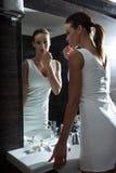 Piękny młodej kobiety kładzenie na makeup w łazience zdjęcie royalty free