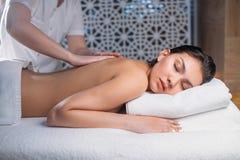 Piękny młodej kobiety lying on the beach na łóżku podczas gdy masażysta masuje ona z powrotem zdjęcie royalty free