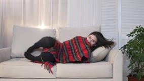 Piękny młodej kobiety lying on the beach na kanapie pod koc w domu i ono uśmiecha się w kamerę zbiory