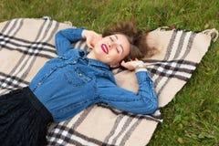 Piękny młodej kobiety lying on the beach na szkockiej kracie w jesień parku Sezon i ludzie pojęć Moda model ma zabawę w spadku pa Zdjęcie Stock