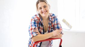 Piękny młodej kobiety mienia farby rolownik i śmiać się w kamerze Zdjęcie Royalty Free