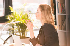 Piękny młodej kobiety mienia ołówek i patrzeć oddalony podczas gdy używać laptop Zdjęcia Stock