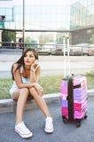 Piękny młodej kobiety obsiadanie, czekanie z walizką i Zdjęcie Royalty Free