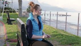 Piękny młodej kobiety obsiadanie na drewnianej ławce na plaży, patrzeje kamerę Zakończenie HD 1920x1080 zbiory