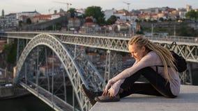 Piękny młodej kobiety obsiadanie na tle Dom Luis przerzucam most w Porto Obrazy Royalty Free