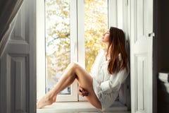Piękny młodej kobiety obsiadanie nadokienny samotnym zdjęcia royalty free