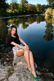 Piękny młodej kobiety obsiadanie rzeką Obrazy Stock