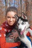Piękny młodej kobiety przytulenia husky szczeniak dla spaceru w parku Zdjęcia Royalty Free
