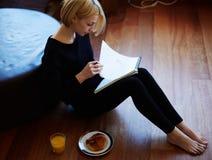 Piękny młodej kobiety writing coś w nutowym ochraniaczu podczas gdy siedzący na podłoga przy żywym pokojem Zdjęcia Stock