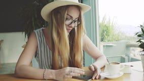 Piękny młody żeński działanie na smartphone w kawiarni Kobieta używa app na telefonie komórkowym i ono uśmiecha się zbiory wideo