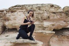 Piękny młody żeński jogger cieszy się odpoczynek po treningu podczas gdy gawędzący na jej telefonu komórkowego obsiadaniu na kami Zdjęcie Royalty Free