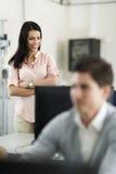 Piękny młody żeński nauczyciel nadzoruje uczeń pracę w cl obraz stock