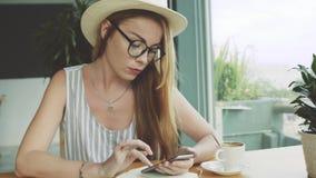 Piękny młody żeński używa telefon komórkowy dla edukaci Poważny kobiety use smartphone w kawiarni zbiory wideo