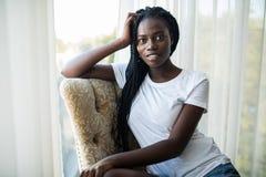 Piękny młody amerykanin afrykańskiego pochodzenia dziewczyny obsiadanie na leżance blisko okno w domu zdjęcie stock