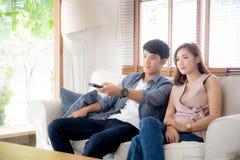 Piękny młody azjatykci pary mienia pilot, dopatrywanie tv i wideo leje się na kanapie z relaksujemy i szczęśliwy obrazy stock