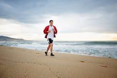 Piękny młody biegacz w sporta czerwonym windbreaker biega wzdłuż plaży na pięknym dennym tle Fotografia Stock