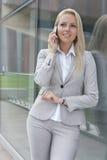 Piękny młody bizneswoman conversing na telefonie komórkowym podczas gdy opierający na szklanej ścianie obrazy royalty free