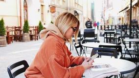 Piękny młody bizneswoman jest ubranym białą koszula i używa nowożytnego mądrze telefon przy przerwą w mieście podczas gdy chodząc zdjęcie wideo