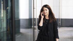 Piękny młody bizneswoman opowiada na odprowadzeniu i telefonie zbiory wideo