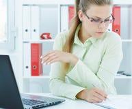 Piękny młody bizneswoman robi notatkom w papierach w biurze Zdjęcia Royalty Free
