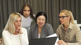 Piękny młody bizneswoman używa laptop podczas biznesowego spotkania z kolegami zdjęcie stock