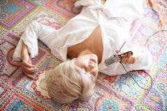 Piękny młody blond kobieta śpiew w błyszczącym mikrofonie kłaść na koc na podłoga obrazy royalty free