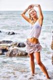 Piękny młody blondynki kobiety pozować plenerowy przy skalistym dennym sho Zdjęcie Stock