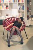 Piękny młody brunetki obsiadanie w bookstore Fotografia Royalty Free