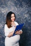 Piękny młody ciężarny bizneswoman trzyma schowek i pisze coś w biel sukni fotografia royalty free