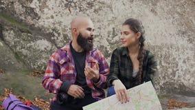 Piękny młody człowiek znosi brodę opowiada joyfully z piękną młodą dziewczyną Turyści siedzieli puszek odpoczywać na kamieniu zbiory