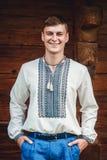 Piękny młody facet w upiększonej koszula na tle drewniany dom zdjęcia royalty free