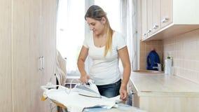 Piękny młody gospodyni domowej odprasowywać czysty odziewa w pralni zbiory