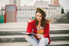 Piękny, młody Kaukaski dziewczyny obsiadanie na ulicznym uśmiechu radość, siedzi z notatnikiem i pisze w Ruhi W czerwonym pulower Obraz Royalty Free