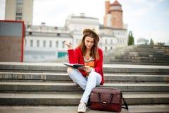 Piękny, młody Kaukaski dziewczyny obsiadanie na ulicznym uśmiechu radość, siedzi z notatnikiem i pisze w Ruhi W czerwonym pulower Zdjęcia Royalty Free